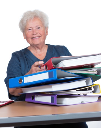 Positive senior woman working part-time in the office to eek out her pension smiling cheerfully from behind a pile of files photo