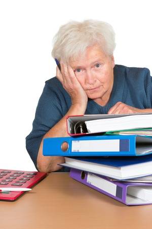 downhearted: Exhausted senior lady leaning on her elbow with a dejected look alongside a huge stack of files and paperwork