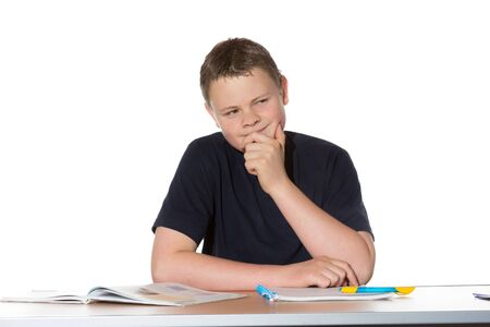 Observant young man sitting at a table with books and a notepad with his chin resting on his hand as he sits thinking and scheming photo