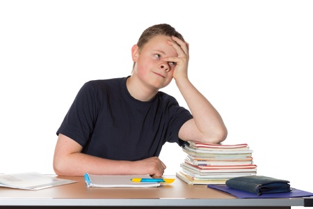 hyperactivity: Handsome young man sitting at a table with books in front of him staring into space with a bored expression suffering from attention deficit hyperactivity disorder or ADHC Stock Photo