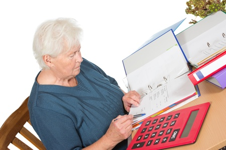 Senior woman sitting at her dining table doing her accounts checking her figures in a file with a large calculator alongside her photo