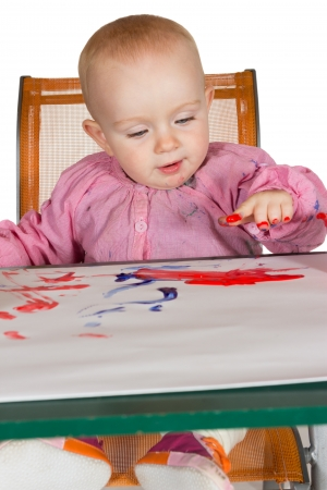 daubed: Adorable little baby girl sitting at a table finger painting with her fingers daubed with red pigment which she is happily painting onto a sheet of paper Stock Photo