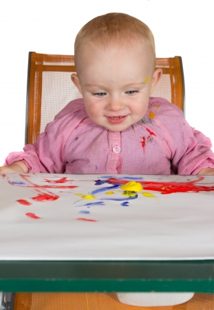 daubed: Happy baby girl sitting at a table with a colourful sheet of paint daubed paper in front of her being creative playing with paint