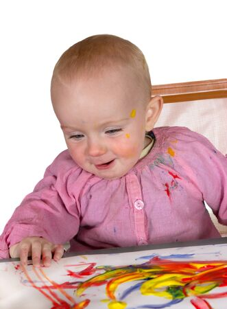 Happy baby girl daubed with colourful red and yellow paint finger painting on a large sheet of paper photo