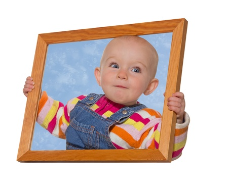framed picture: Cute little baby girl holding an empty wooden picture frame around her head with blue sky inside the surround isolated on white Stock Photo