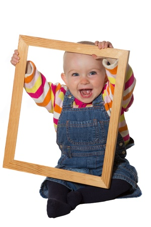 vivacious: Laughing vivacious little baby girl playing with an empty wooden picture frame looking through it at the camera