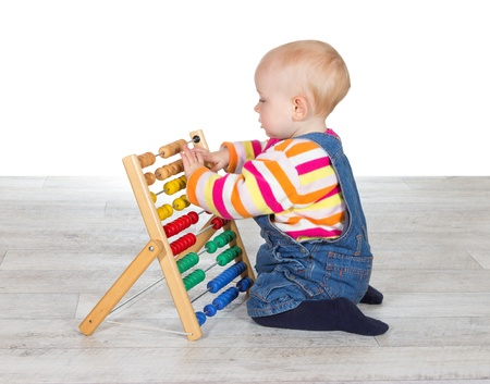 Cute little baby girl kneeling on the floor in dungarees playing with a colourful abacus moving the counters as she learns