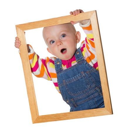 Little baby girl holding up an empty wooden picture frame around her face with a look of amazement isolated on white photo