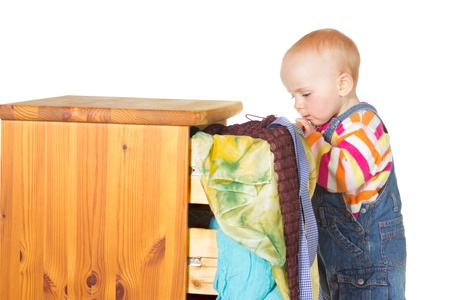 Curious little baby standing peering into a drawer with colourful textiles spilling out onto the floor on a white background