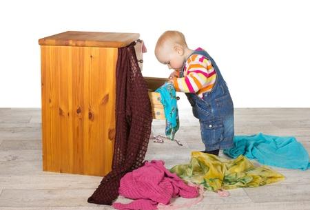 Bonne recherche permanente bébé dans un tiroir d'un petit coffre en bois à tiroirs déballage des vêtements colorés et des textiles sur le sol dans un tas aléatoire Banque d'images