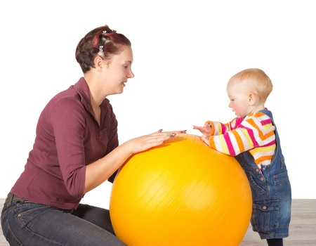 Mother encouraging her young toddler, who has delayed motor activity disability, to stand using a gym ball
