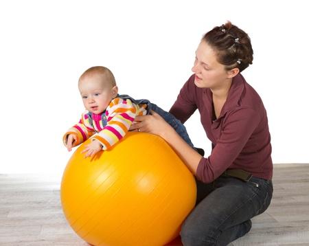 interventie: Baby met vertraagde motorische activiteit ontwikkeling wordt ondersteund op de top van een gele pilates bal door zijn zorgzame moeder in een poging om spier respons te stimuleren Stockfoto