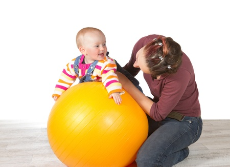stimulation: Devoted mother exercising her laughing baby who has late development of motor activity using a yellow pilates ball Stock Photo