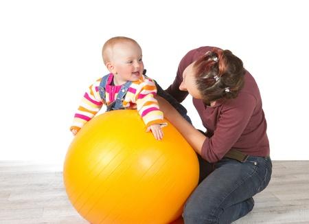 Mère dévouée exercer son bébé rire qui a le développement tardif de l'activité motrice à l'aide d'un jaune pilates ball