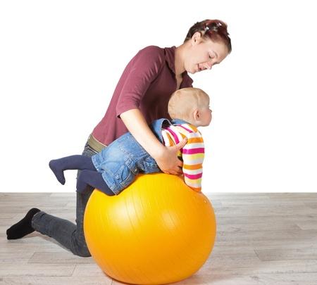 Madre joven el ejercicio de su bebé apoyándolo sobre una pelota de gimnasio para estimular la coordinación muscular y el movimiento debido al desarrollo tardío de las habilidades motoras