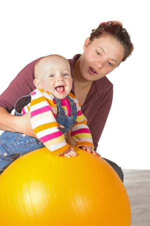 Laughing baby with delayed motor activity development doing exercises with the support of its mother and a yellow gym ball to strengthen muscles and develop coordination of motion photo