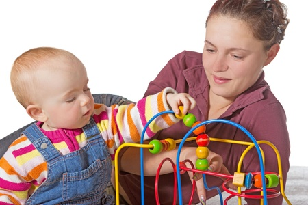 Baby with motor activity development delay being stimulated to develop muscle coordination and movement on a bead maze watched by a devoted mother photo