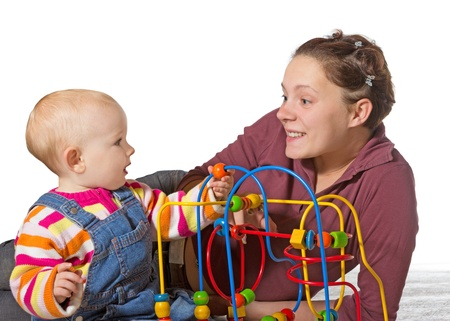 delay: Baby with motor activity development delay being stimulated to develop coordination and muscle control and movement on a bead maze by an adoring mother Stock Photo