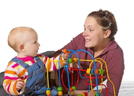 discapacidad: Bebé con retraso en el desarrollo de la actividad motora está estimulando el desarrollo de la coordinación y el control de los músculos y el movimiento en un laberinto talón por una madre que adora Foto de archivo