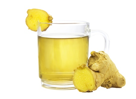 ginger plant: Cut rhizome of fresh root ginger, or Zingiber officinale, with a glass of fresh infusion or tea used to aid weight loss and as a treatmet for dyspepsia, on a white background Stock Photo
