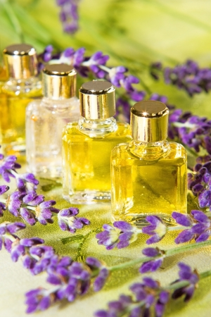 volatile: Golden plant extracts and essential oils in clear glass bottles for use in aromatherapy and perfumery surrounded by fresh purple blossom