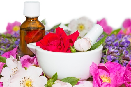 ceramic bottle: Essential oil and rose blossoms in mortar used in aromatherapy and spa Stock Photo