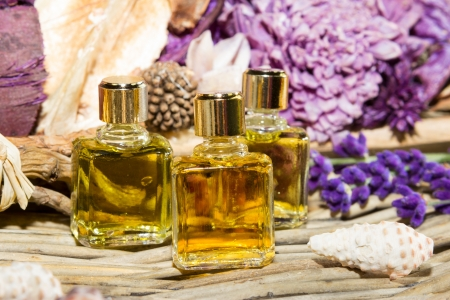 perfumery: Essential oil or perfume, with lilac blossoms on a wooden background