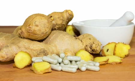 Fresh root ginger with whole and sliced rhizomes alongside a white ceramic pestle and mortar and a pile of capsules conceptual of plant extracts and supplements Stock Photo - 20873920