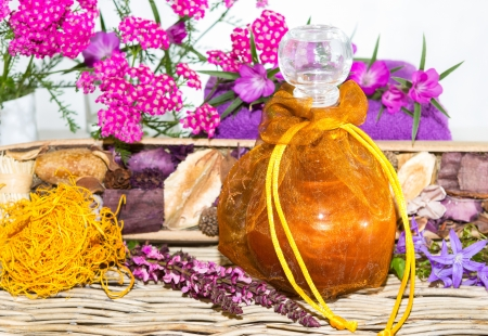 Bath oil or Essential oil with herbs and blossoms photo