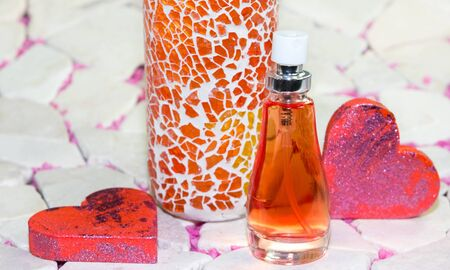 atomiser: Beautiful Valentines gift of a special perfume with a brightly coloured speckled orange box standing flanked by two romantic red hearts Stock Photo