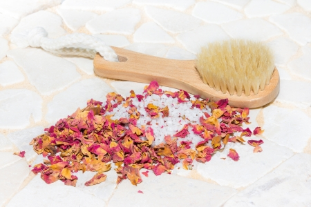 Pile of crystallised bath salts ringed with fragrant dried pink rose petal potpourri alongside a wooden bathing brush for a luxury bath experience photo