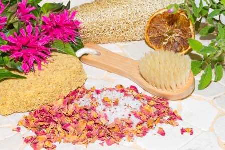 bee balm: Luxury aromatic bathing accessories with crystallised bath salts surrounded by fragrant dried rose petals, fresh bee balm flowers,a sponge, brush and loofa Stock Photo
