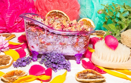 Colourful conceptual luxury bathing still life with a miniature bathtub filled with bathsalts and dried rose petals surrounded by fresh fragrant flower petals, lavender and dried orange slices photo