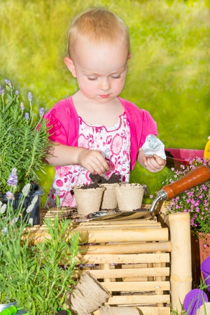 Pretty little girl in a pink floral dress gardening in the sunshine standing potting plants and inserting labels into the soil in the flowerpots photo