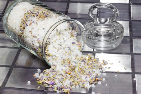 bathsalt: Dried potpourri with a natural fragrance to refresh the air in your home made from a mixture of natural flowers, plant shavings and spices spilling out of a glass jar onto a tiled grey surface Stock Photo
