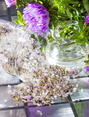 bathsalt: Floral aromatic potpourri with a sweet fragrance made from a mixture of natural flowers, plant shavings and spices spilling out of a glass jar onto a tiled surface with a bunch of fresh purple flowers