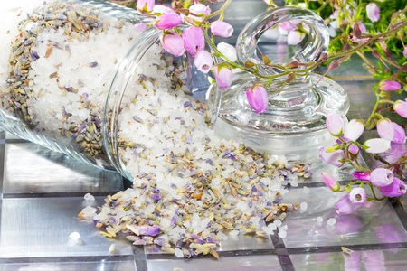 fragrant scents: Closeup view of natural floral potpourri with a fresh aromatic scent to refresh the air in your home spilling out of a glass container onto a tiled surface with a spray of pretty delicate pink flowers