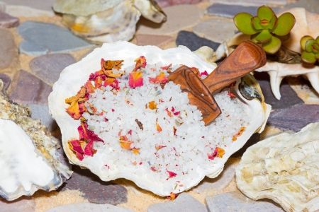 replenishment: Marine sea salt with dried rose flower petals for mineral replenishment and detoxifying of the skin and body in a luxury bath treatment at the spa or home Stock Photo