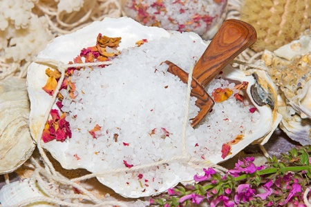 crystal therapy: Healthy marine bath salts rich in minerals mixed with dried aromatic rose petals for a luxury bath treatment at a spa