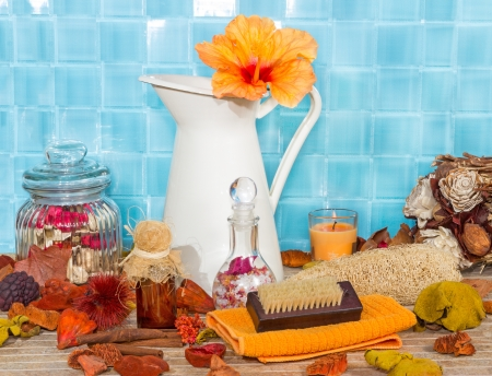 Exotic spa bathing accessories with an orange hibiscus flower in a jug against turquoise blue tiles with rose petal potpourri , bath salts, sponges and a variety of luxury bathing accessories photo