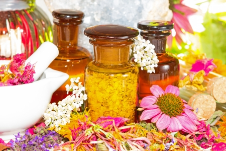 Aromatherapy still life with fresh flowers, a ceramic pestle and mortar and brown glass jars filled with dried petals and plant extracts for a healing relaxing treatment or therapeutic massage photo