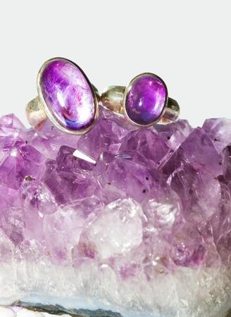 crystal healing: Cristalli di ametista che fanno parte di un geode con due anelli con cabochon di ametista lucido, una forma viola di quarzo viene utilizzato nella guarigione di cristallo come un trattamento contro la dipendenza - la pietra sobriet�