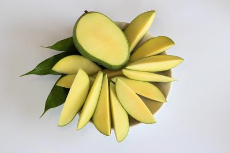 peeled raw mango and mango leafs on a plate