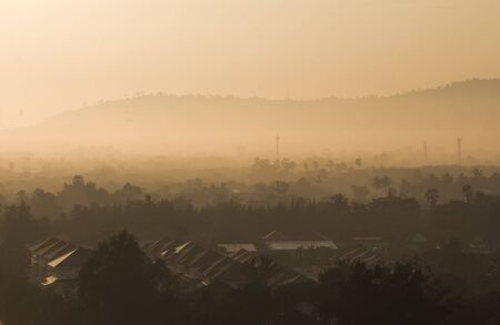rural skyline: beautiful fog and morning orange color sunlight above thailand rural city,suratthani province
