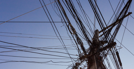 unorganized: chaotic wire on pole and blue sky background Stock Photo
