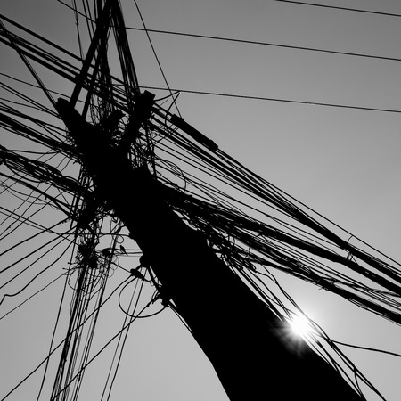 wire mess: chaotic wire on pole with sunlight on sky background in black and white