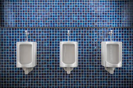 mensroom: white urinal in men public toilet with blue wall tile