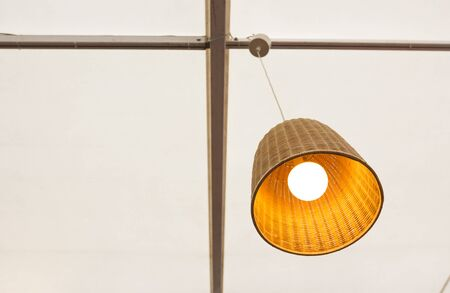 Weaved wooden lamp and yellow bulb hanging from ceiling Stock Photo