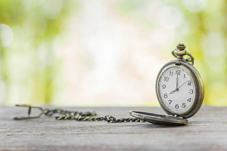 vintage chain watch on wooden  table with blur natural background