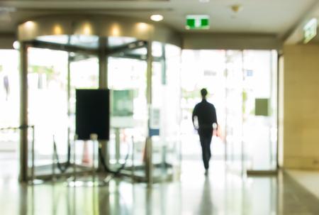 people walking pass the glass door in office building
